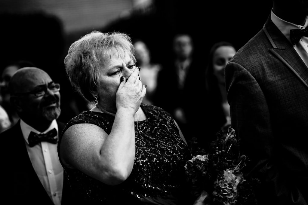 Mother crying while looking at bride